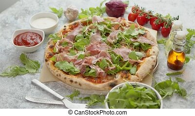 Pizza with prosciutto and arugula. Served with fresh ...