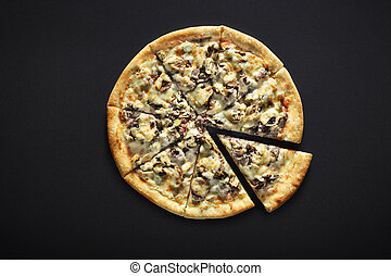 Pizza with raw minced meat on a black stone background