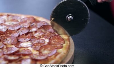 Pizza with salami cut in half with a special knife for pizza.