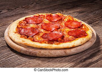 Pizza with salami on the old board