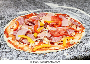 Pizza with sausages, sliced pepper and tomatoes.
