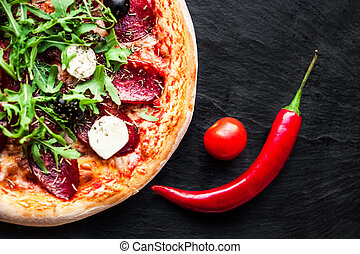 Pizza with tomatoes, cheese, red chilli pepper, herbs and ...