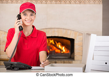 Pizzeria - Happy delivery woman of pizza in red uniform with...