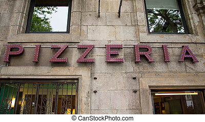 Pizzeria Sign - A lighted pizzeria sign on a building over a...