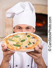 Pizzeria - Young cook with pizza margherita. Close-up.