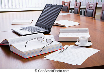 Place of work - Opened thick books and laptop, documents, ...