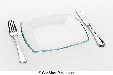 Place setting for one person. Knife, square glass plate and fork.