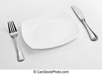 Place setting for one person. Knife, square white plate and fork.