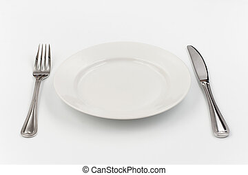 Place setting for one person. Knife, white plate and fork. -...