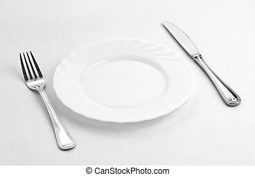 Place setting for one person. Knife, white plate and fork.