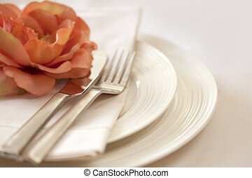 Place setting in soft focus, with delicate peach flower. shallow depth of field.