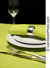 place setting with green tablecloth and glass and silverwarre