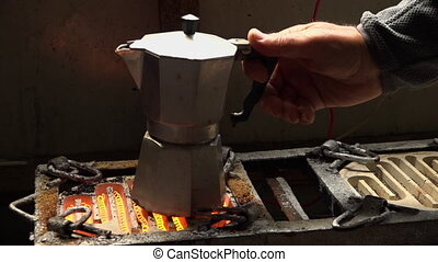 Placing a coffee pot on a red hot coil stove - A man's hand...