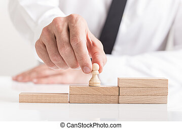 Placing a pawn chess piece on wooden steps