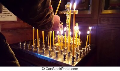 Placing candles people ask god for forgiveness and well-being. Holy faces in the Icon on a background