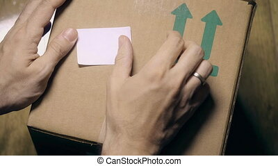 Placing FORWARDING sticker on a carton - Labeling carton...
