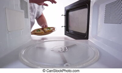 Placing toasts with cheese in the microwave oven