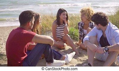 plage., groupe, séance gens, jeune, sablonneux