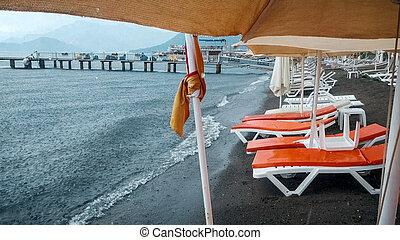plage., pluie, sunbeds, vide, mer, mouillé, fort, parapluies
