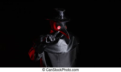 Plague doctor with crow-like mask disapproving with no finger sign, make negation gesture. Denying, Rejecting, Disagree isolated on black background. Creepy mask, historical costume concept. Epidemic.