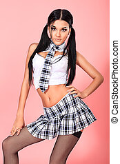 plaid - Sexy student girl posing over pink background.