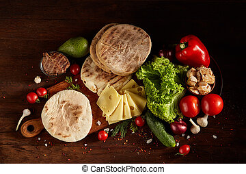 Plain pita on a cutting board with fresh vegetables and cheese on a wooden background, flat lay, selective focus.