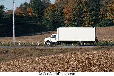 A plain white cube van speeding on a road during the harvest.