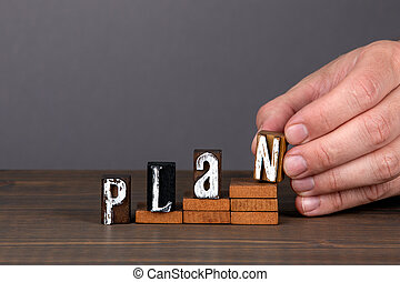 PLAN. Future, new year and business concept. Wooden alphabet letters on steps