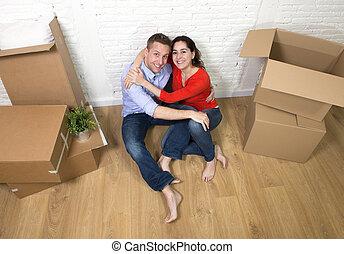 plancher, maison, couple, séance, jeune, célébrer, en mouvement, nouveau, heureux
