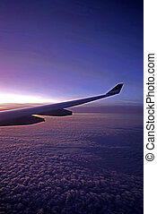 Plane, aeroplane wing, clouds, gradient sky from aerial view...