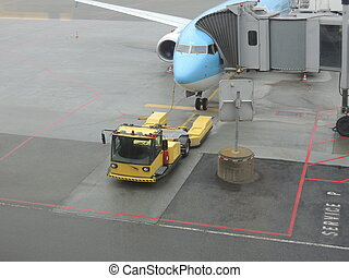 Plane at gate with yellow tow truck