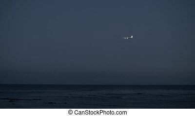 Plane coming in for a landing over the ocean, evening view