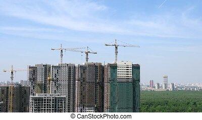 Plane flies above apartment buildings construction site,...
