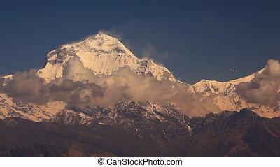 Plane flies against Dhaulagiri peak (8167 m) in Himalayas.