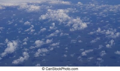Plane flies highly over Earth and clouds