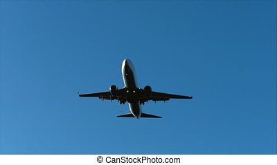 plane flies in a blue sky with clouds overhead, preparing to land at the airport at sunset or sunrise.