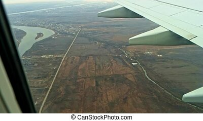 Plane fly over land with rivers and fields