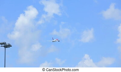 Plane flyes in clear blue cloudy sky