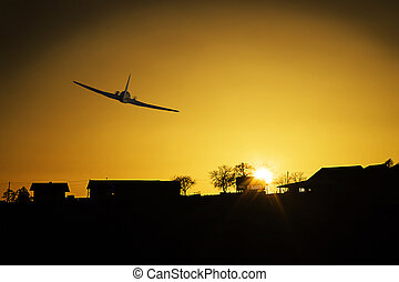 Plane flying above house silhouette.