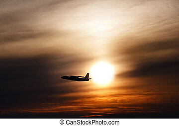 plane flying at sun in sunset sky. airplane in the air. transportation concept with space for text.  Silhouette of a big passenger or cargo aircraft in sun light and clouds.