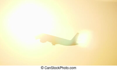 Plane flying in evening sky against sun flare - Black...
