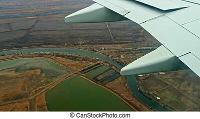 Plane flying over rural area with rivers.