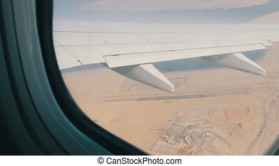 Plane is flying over the desert. Wing an airplane out the window on a background of a desert yellow landscape