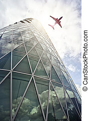 plane over office tower - plane flying over a modern glass...