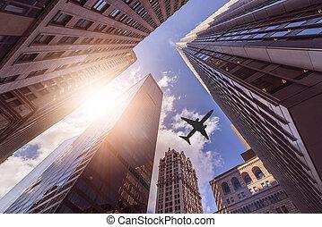 plane over skyskrapers - plane flying over multiple office...