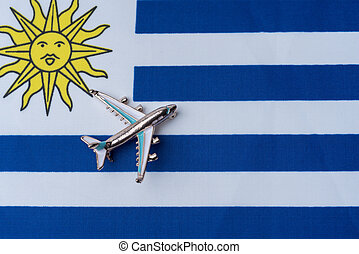Plane over the flag of Uruguay travel concept.