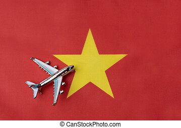 Plane over the flag of Vietnam travel concept.