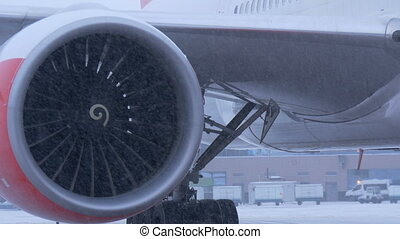 Plane parked at the airport. Ready to fly. The turbine close-up. In winter snow storm.