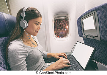 Plane passenger business woman professional working in airplane cabin during flight with in-flight wifi typing writing on tablet computer listening to music with headphones. Young Asian traveler
