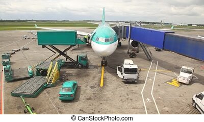 plane standing at airstrip is loaded with goods by airport...
